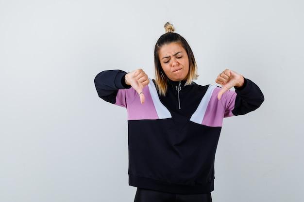 Ładna kobieta pokazująca kciuki w dół w bluzie i wyglądająca na niezadowoloną