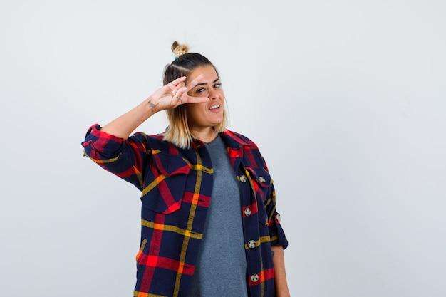 Ładna kobieta pokazująca znak v w pobliżu oka w swobodnych ubraniach i patrząca wesoło