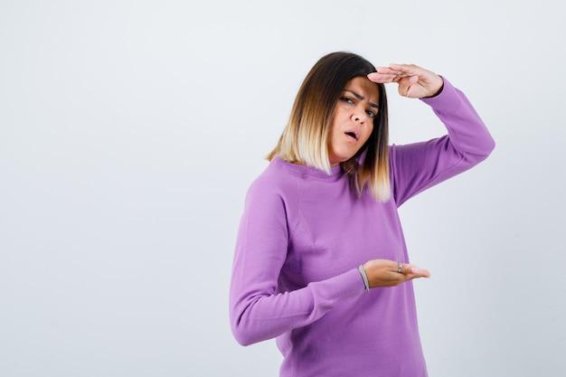 Ładna kobieta pokazuje duży znak w fioletowym swetrze i wygląda na zdziwioną. przedni widok.