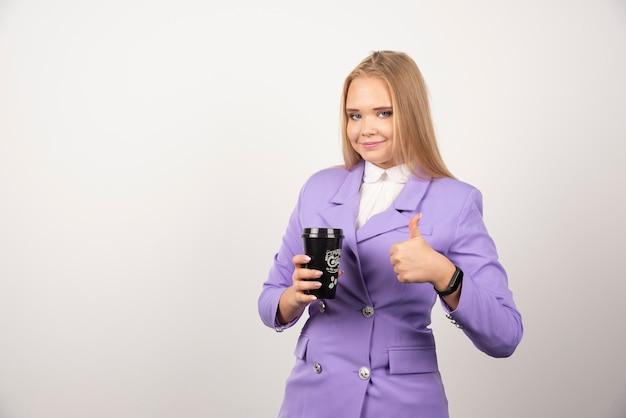 Ładna kobieta pokazuje filiżankę kawy na białej ścianie.