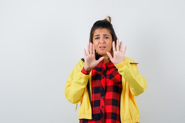 Ładna kobieta pokazuje gest stop w koszulę, kurtkę i przestraszony. przedni widok.