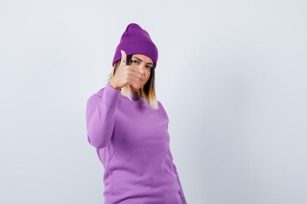 Ładna kobieta pokazuje kciuk w sweter, czapka i patrząc na szczęście, widok z przodu.