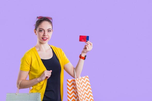 Ładna kobieta pokazuje prezent kartę z mienie torba na zakupy przed purpurową ścianą