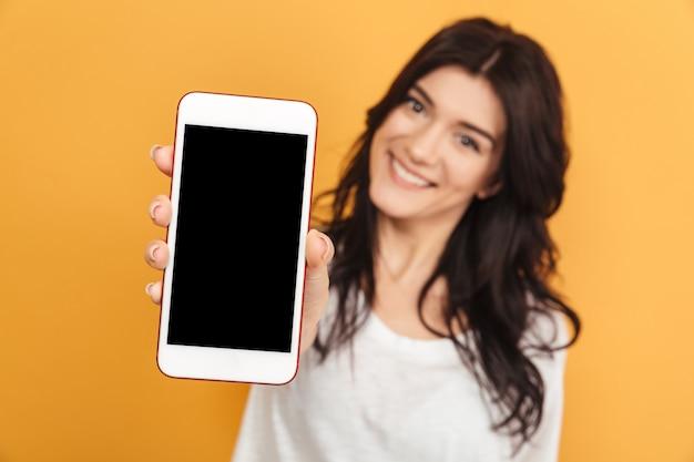 Ładna kobieta pokazuje wyświetlacz telefonu komórkowego.