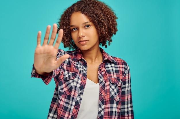 Ładna kobieta pokazuje znak stopu, niebieska ściana, emocje
