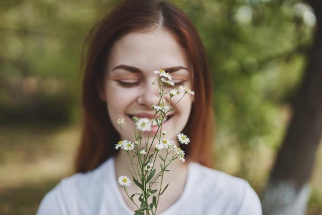 Ładna kobieta polne kwiaty natura słońce wolność podróż. zdjęcie wysokiej jakości