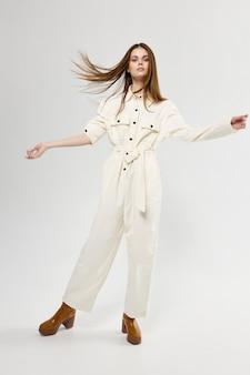 Ładna kobieta potargane włosy biały kombinezon moda.