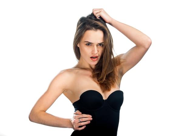 Ładna kobieta pozowanie w czarny top na białym tle. kobieta o długich ciemnych włosach położyła rękę nad głową.
