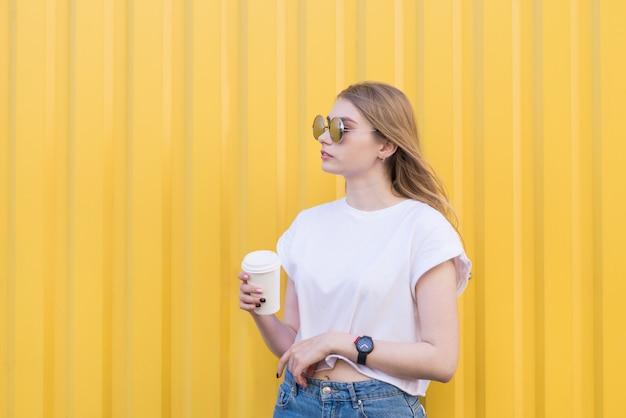 Ładna kobieta pozuje dla filiżanki kawy w ręce na żółtej ścianie.