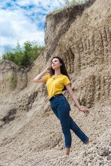 Ładna kobieta pozuje na tle piaskowego kanionu skał w gorący letni słoneczny dzień