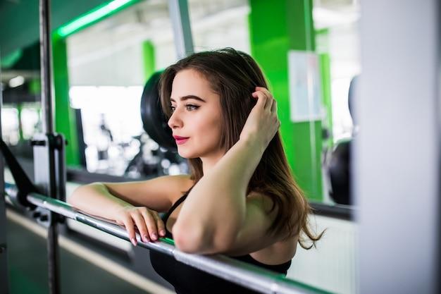 Ładna kobieta pozuje w klubie sportowym ze sztangą