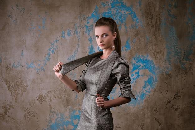 Ładna kobieta pozuje w sukience na ścianie grunge