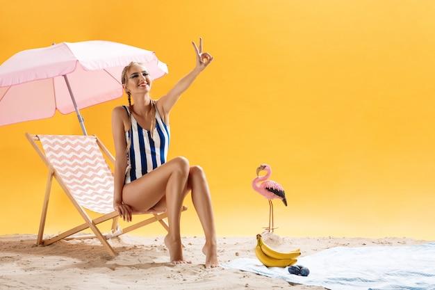 Ładna kobieta pozuje w swimsuit w studiu, pokazuje pokoju znaka