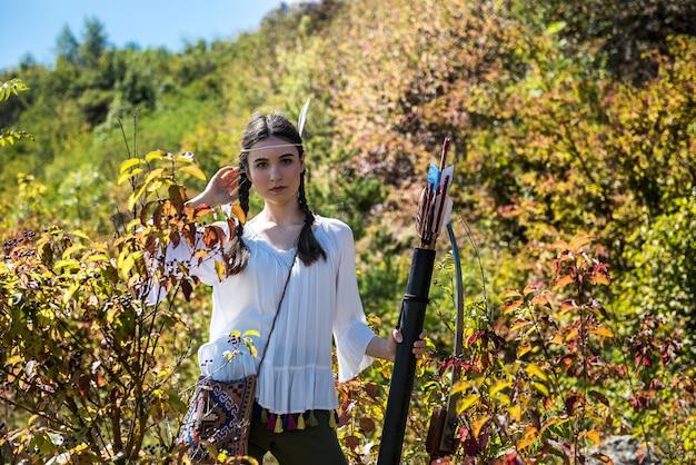 Ładna kobieta pozuje w tradycyjnym stroju i broni jako indiański wojownik na zewnątrz