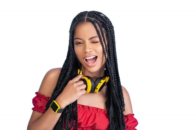Ładna kobieta pozuje w żółtych hełmofonach i wristwatch na bielu