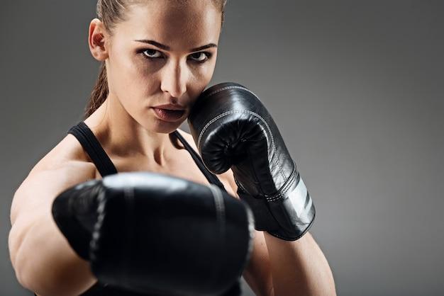 Ładna kobieta pozuje z bokserskimi rękawiczkami