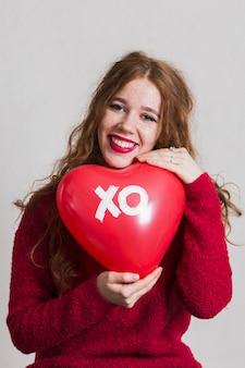 Ładna kobieta pozuje z kierowym balonem