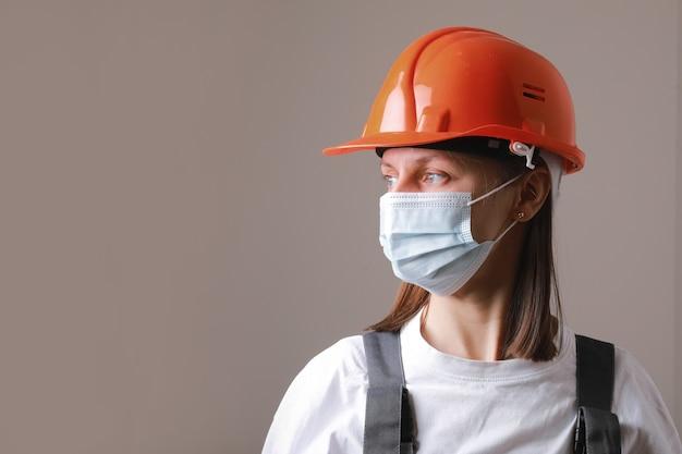 Ładna kobieta pracownik w masce medycznej i hełmie budowy pomarańczowy na szarym tle.