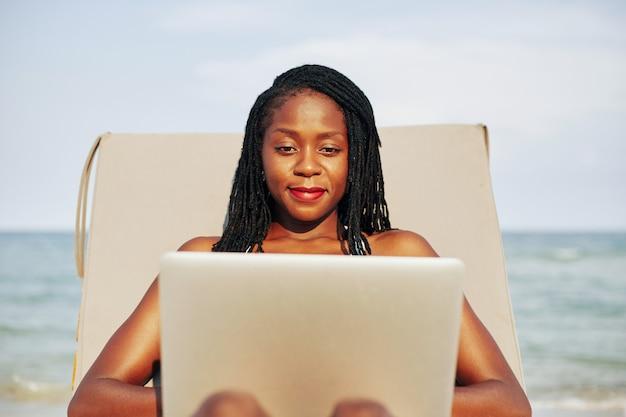 Ładna kobieta pracuje na laptopie na plaży