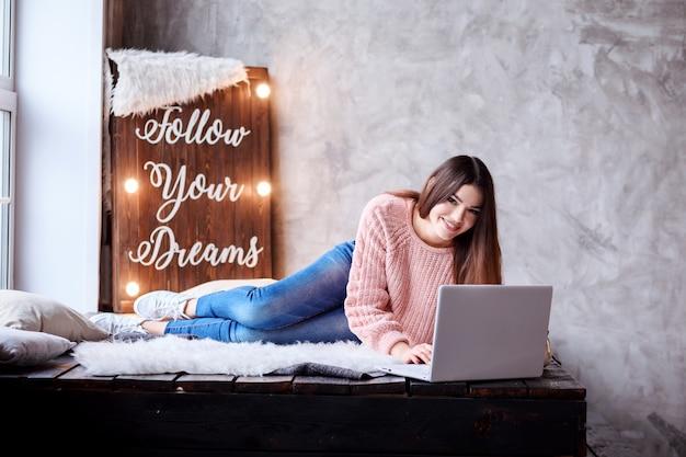 Ładna kobieta pracuje w domu na swoim laptopie. spędzanie czasu w domu, pisanie w notatniku, komunikowanie się na komputerze. panel świetlny podążaj za marzeniami za dziewczyną.