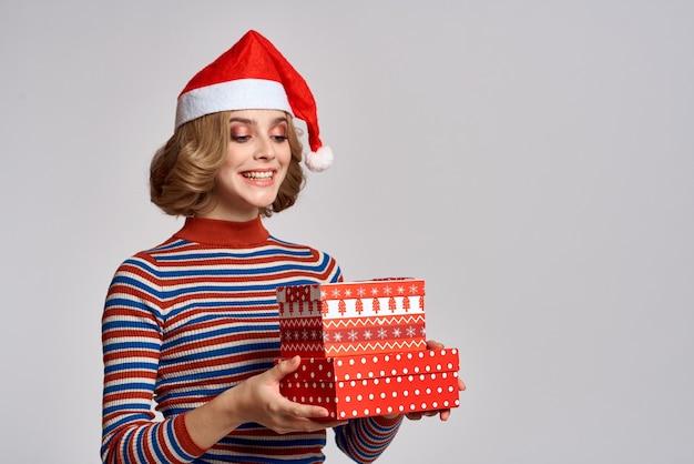 Ładna kobieta prezenty świąteczne zabawa dekorowanie santa hat. wysokiej jakości zdjęcie