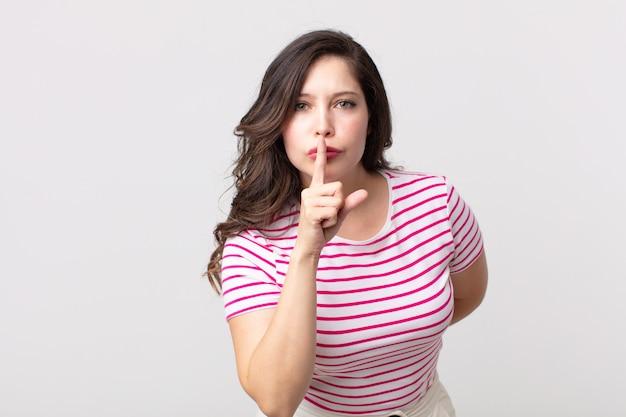 """Ładna kobieta prosząca o ciszę i spokój, gestykulująca palcem przed ustami, mówiąca """"cii"""" lub dochować tajemnicy"""