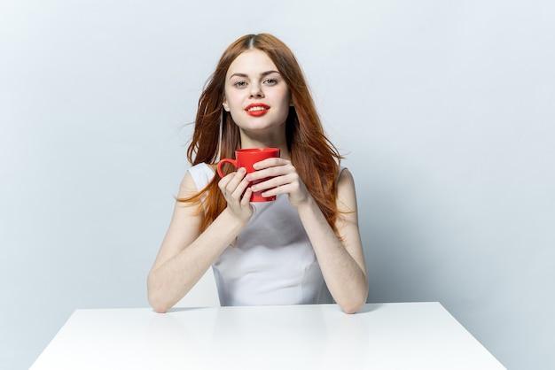 Ładna kobieta przy stole z czerwonym kubkiem w ręce urok.