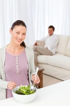 Ładna kobieta przygotowywa sałatki w kuchni dla jej chłopaka