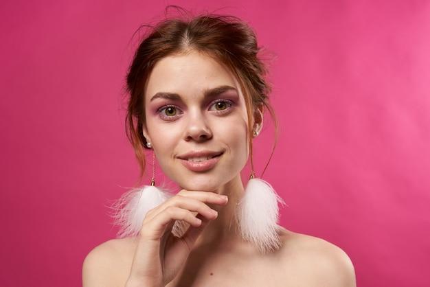 Ładna kobieta puszyste kolczyki jasny makijaż różowe tło. wysokiej jakości zdjęcie