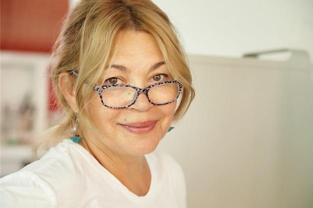 Ładna kobieta rasy kaukaskiej w średnim wieku o blond włosach i miłych oczach, patrząca z czułym i przyjaznym uśmiechem, czekając, aż wnuki odwiedzą ją w domu podczas letnich wakacji