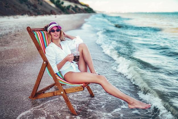Ładna kobieta relaksuje na leżak plaży i pije sodę