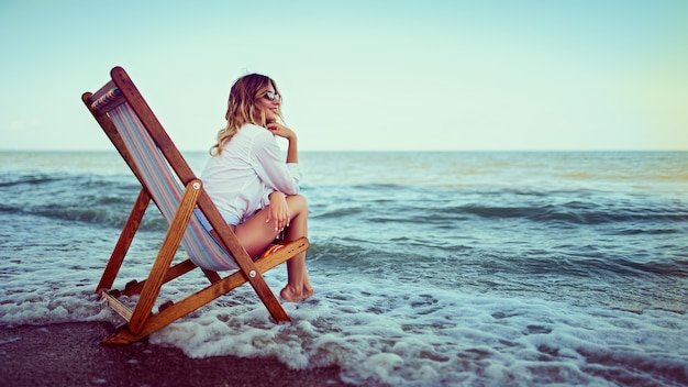 Ładna kobieta relaksuje na leżak plaży