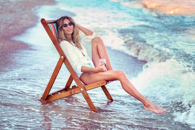Ładna kobieta relaksuje na lounger plaży i pije sodowanej wody wakacje pojęcie.