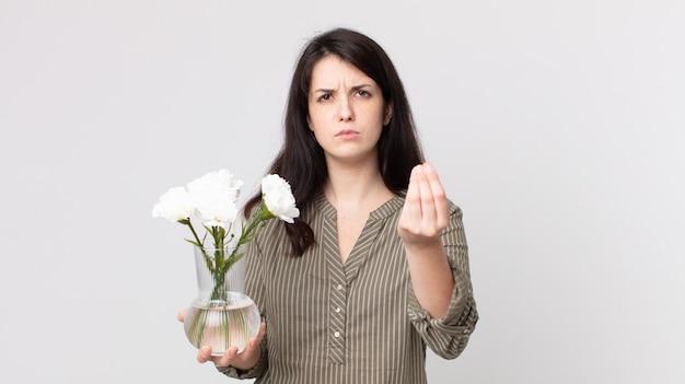 Ładna kobieta robi gest kaprysu lub pieniędzy, każe ci zapłacić i trzyma ozdobne kwiaty. asystent agenta z zestawem słuchawkowym