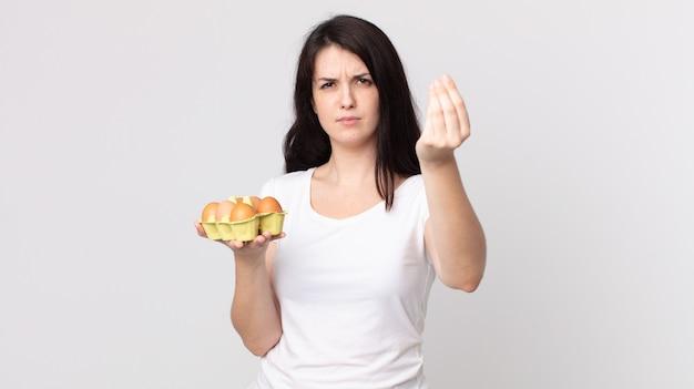 Ładna kobieta robi gest kaprysu lub pieniędzy, każe ci zapłacić i trzyma pudełko z jajkami