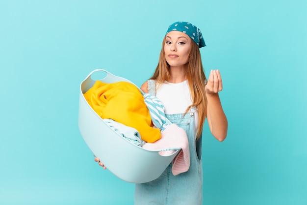 Ładna kobieta robi gest kaprysu lub pieniędzy, każe ci zapłacić, trzymając kosz do prania