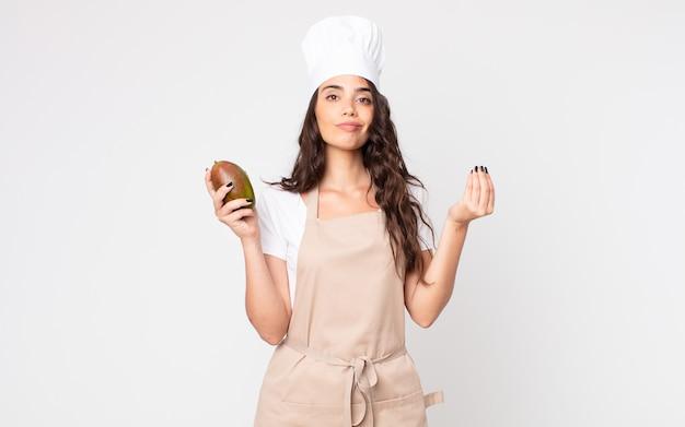 Ładna kobieta robi gest kaprysu lub pieniędzy, mówiąc, że musisz zapłacić, mając na sobie fartuch i trzymając mango
