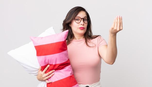 Ładna kobieta robi gest kaprysu lub pieniędzy, mówiąc, że musisz zapłacić, mając na sobie piżamę i trzymając poduszkę