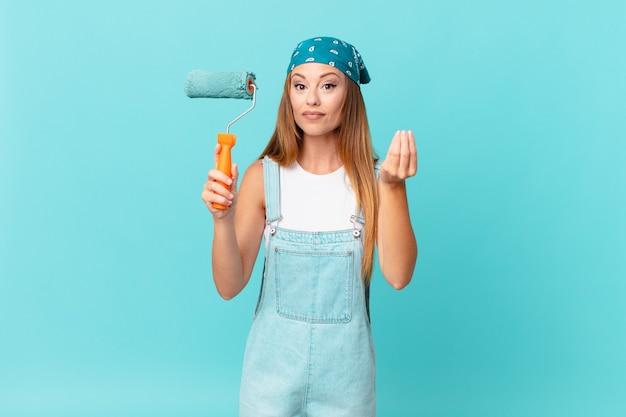 Ładna kobieta robi gest kaprysu lub pieniędzy, mówiąc, że musisz zapłacić za malowanie nowej ściany domu