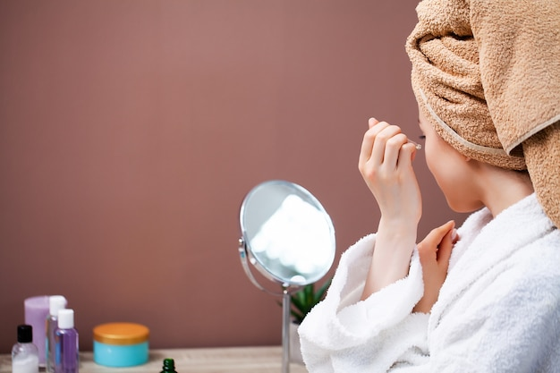 Ładna kobieta robi kosmetyczne procedury w domu przed lustrem