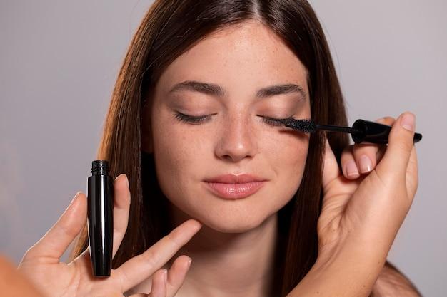 Ładna kobieta robi makijaż przez profesjonalistę