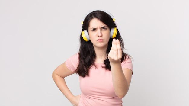 Ładna kobieta robiąca gest kaprysu lub pieniędzy, mówiąca ci, aby zapłacić słuchając muzyki przez słuchawki