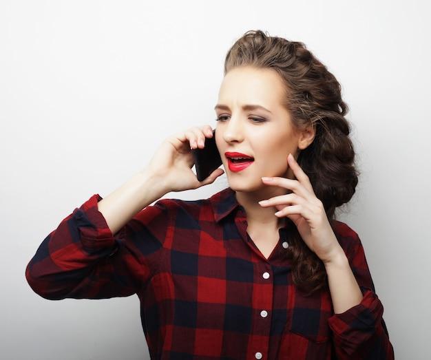 Ładna kobieta rozmawia przez telefon na białej powierzchni