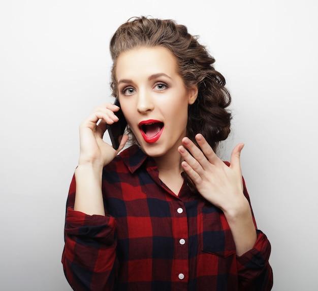 Ładna kobieta rozmawia przez telefon na białej ścianie