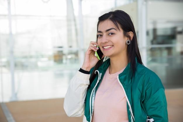 Ładna kobieta rozmawia przez telefon, patrząc na kamery, uśmiechając się