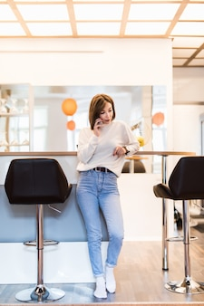 Ładna kobieta rozmawia przez telefon stojący w panoramicznej kuchni z jasnymi ścianami, wysokim stołem i krzesłami barowymi