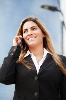 Ładna kobieta rozmawia z telefonu komórkowego w środowisku miejskim