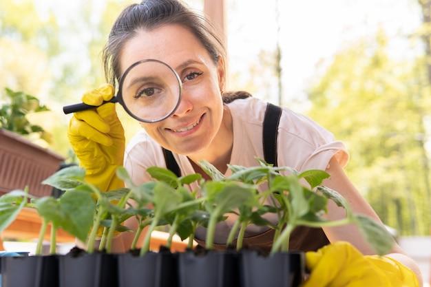 Ładna kobieta sadzi sadzonki w ogrodzie