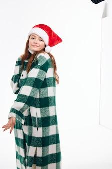 Ładna kobieta santa hat uśmiech kratę płaszcz studio. wysokiej jakości zdjęcie