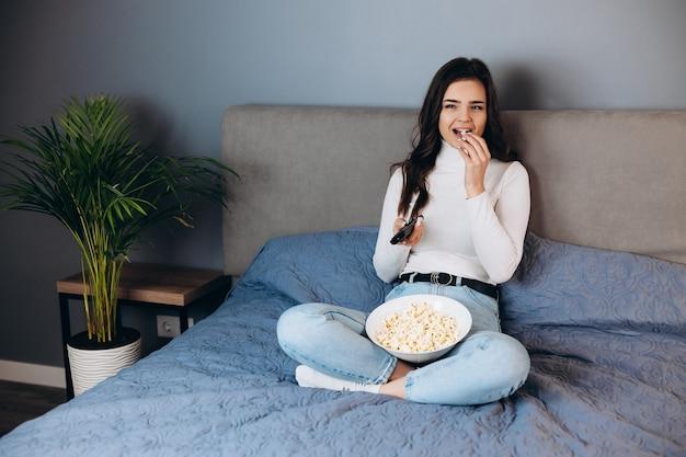 Ładna kobieta się uśmiecha. ładna kobieta ma czas wolny w kwarantannie oglądaj film pod wrażeniem nieoczekiwanego filmu / zakończenia filmu trzymaj duże pudełko na kukurydzę siedzieć na kanapie w domu w domu.